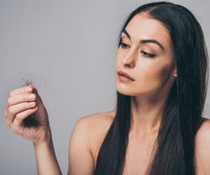 Braunhaarige Frau leidet unter Haarbruch