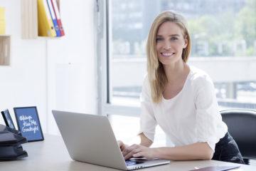Blonde lächelnde Frau am Laptop