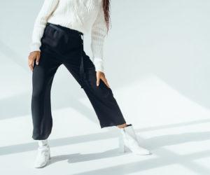Model mit Dunkler Hose vor weißen Wand