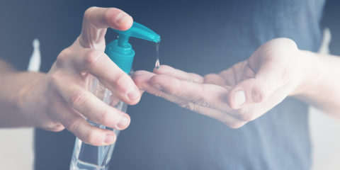 Male hand using sanitizer to disinfect from Covid-19 bacteria.