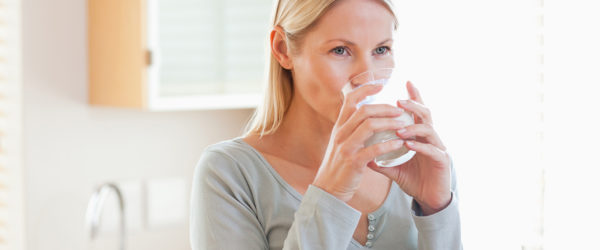 Woman in the kitchen drinking water