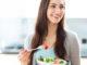 braunhaarige Frau mit Schüssel Salat in der Hand