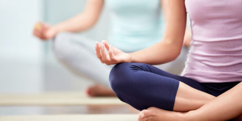 Zwei Frauen, welche auf dem Boden sitzen und Yoga machen