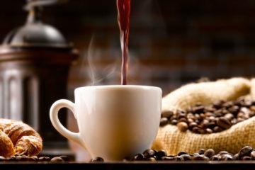 Tasse Kaffee im Setting zwischen Kaffeebohnen und Kaffeemühle
