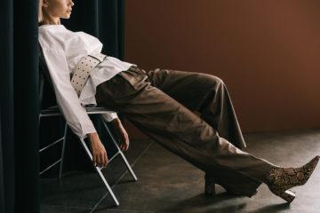 Frau mit brauner Hose und weißer Bluse sitzt auf Stuhl