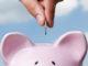 Hand die in Sparschwein Münze einwirft