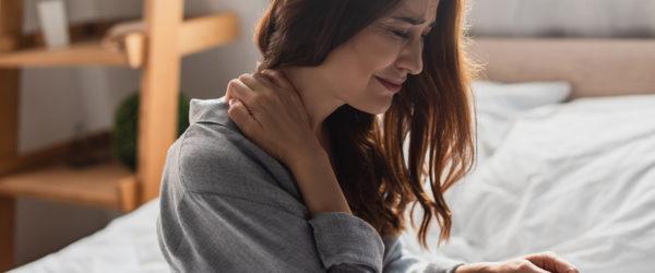 Frau die auf Bett sitzt und sich schmerzhaft an den Nacken fast