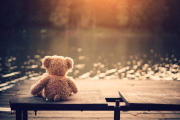 Teddy Bär sitzt einsam auf einer Bank an einem See